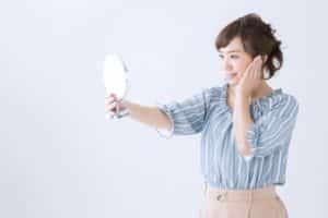 鏡を見て満足そうな女性