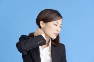 首が痛くて首に手を当てる女性