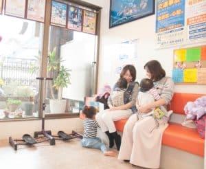待合室で子供と一緒に待つ母親と友人