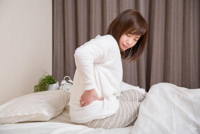 寝起きで腰の痛みがつらい女性
